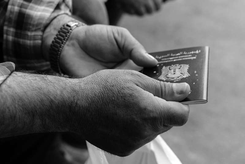 A Syrian man holds his passport outside the Syrian consulate in Istanbul on May 4, 2017