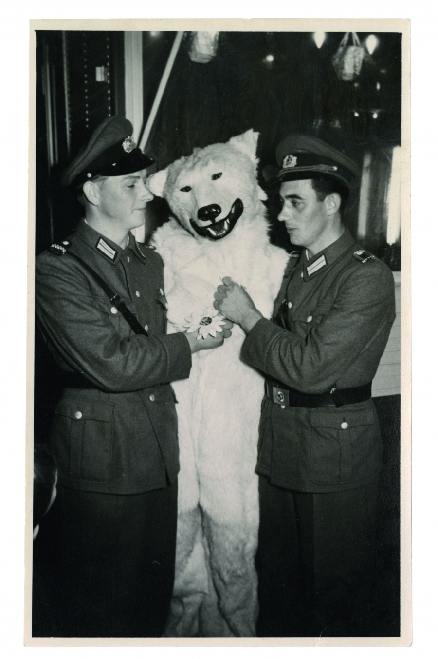 A smiling polar bear sandwiched between two German soldiers in Wehrmacht uniforms.