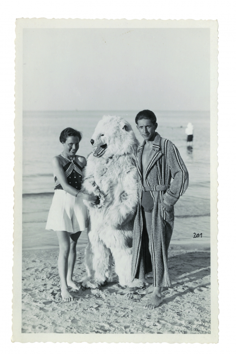 A man in a polar bear suit poses with a young German couple