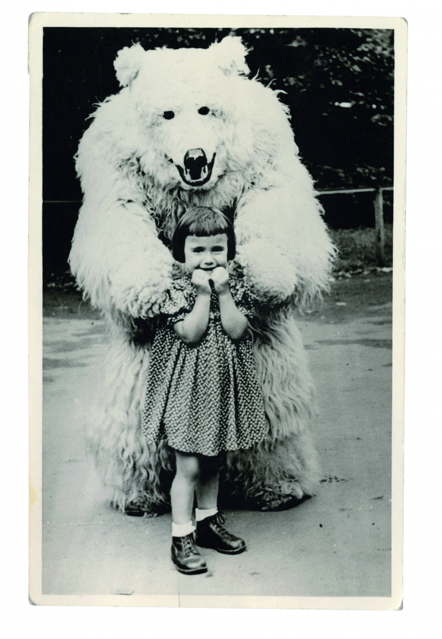 A young German girl stands with a man in a polar bear costume