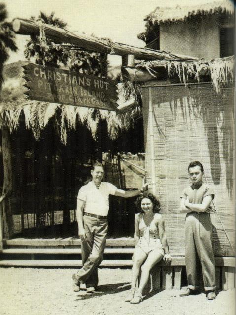 Black and white photo of three people in front of bar entrance, island scene