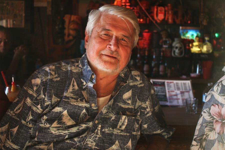 Smiling man in Hawaiian button-down shirt, looking at camera