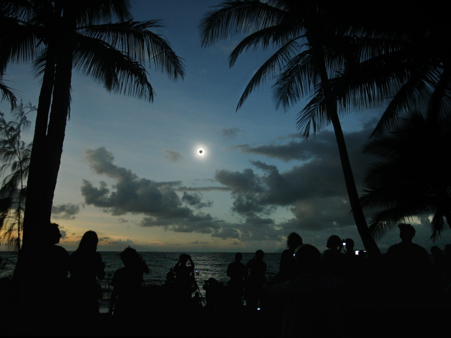 A crowd of people are gathered to watch a total solar eclipse surrounded by tall palm trees. In the center, the total eclipse hangs over the ocean. The moon is a black dot surrounded by a white glowing light and the sky is a deep blue.