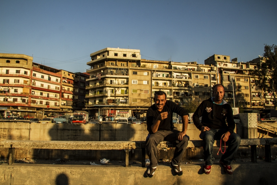 Bab al-Tabbaneh residents Usama and Hussein sit on a railing at the edge of the neighborhood. They say for men like them with families to support there isn't enough work in Tripoli and while they're against extremist groups like the Islamic State, they ca