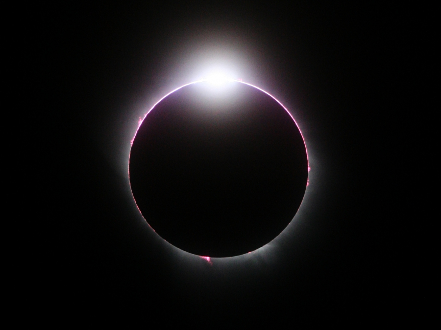 A close-up image of a total solar eclipse is mostly black with just a hint of light peeking around the sun with a bright burst of white light at the top
