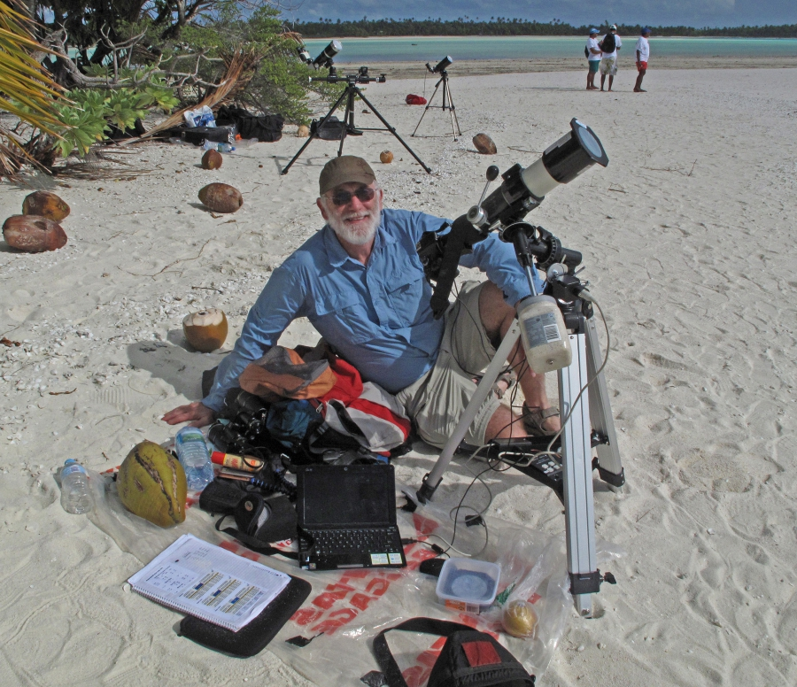 Terry Cutler wears a blue shirt and khaki shorts and on a sandy beach with a bunch of photography equipment for taking pictures of eclipses.