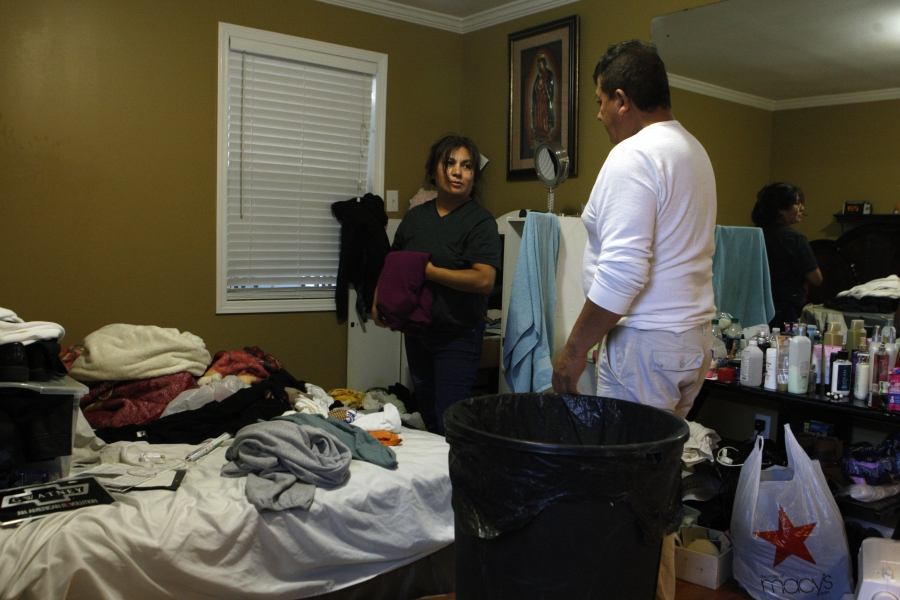 Man and woman looking at clothes and items strewn across a bed, being put in bags