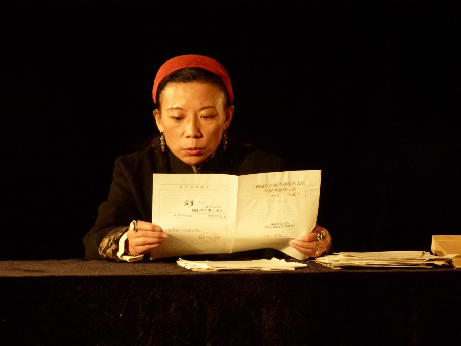 """Tibetan writer Tsering Woeser reads from a government document about her activities in Zhu Rikun's film, """"The Dossier."""""""