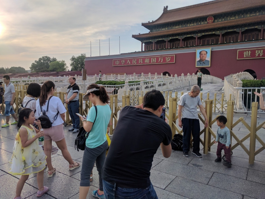 Chinese pose for photos near Mao Zedong's photo at the entrance to the Forbidden City in Tiananmen Square, Beijing