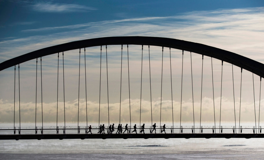 A group of joggers run across the Humber Bay Arch Bridge during extreme cold temperatures in Toronto.