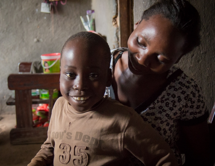 Nine-year old Steven Mafabi sits on his mother's lap. He was treated for hydrocephalus as an infant at the CURE Children's Hospital in Mbale, Uganda.