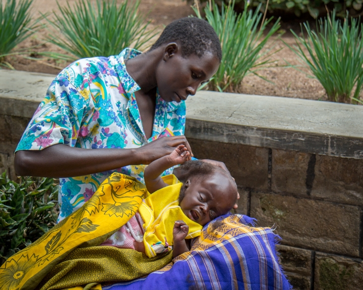 Outside the hospital, a mother shaves her child's head in preparation for neurosurgery.