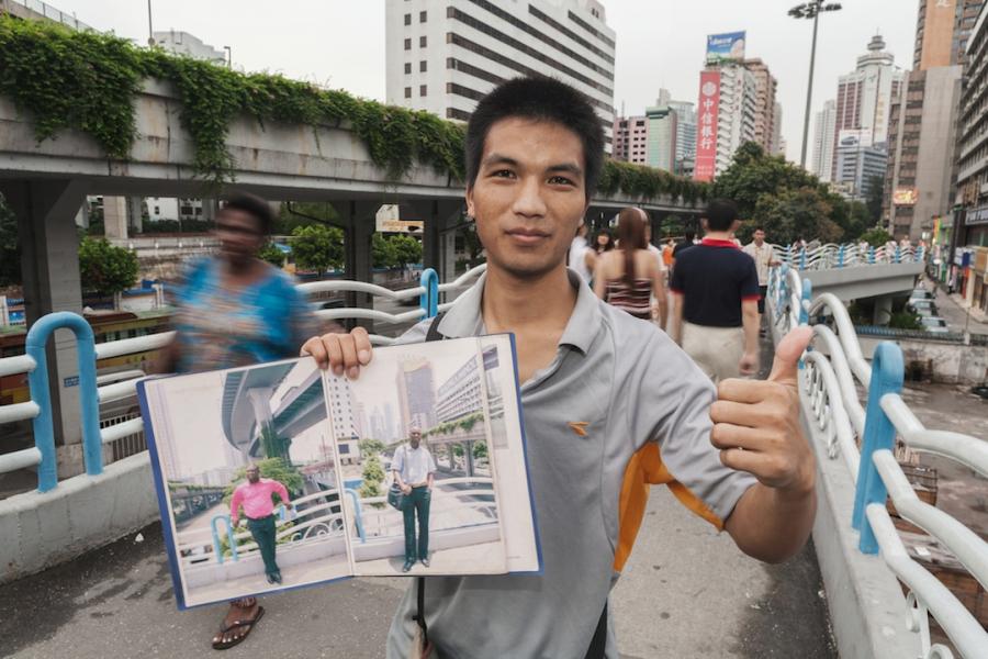 Wu Yong Fu holding portrait album on the bridge, July 30, 2009