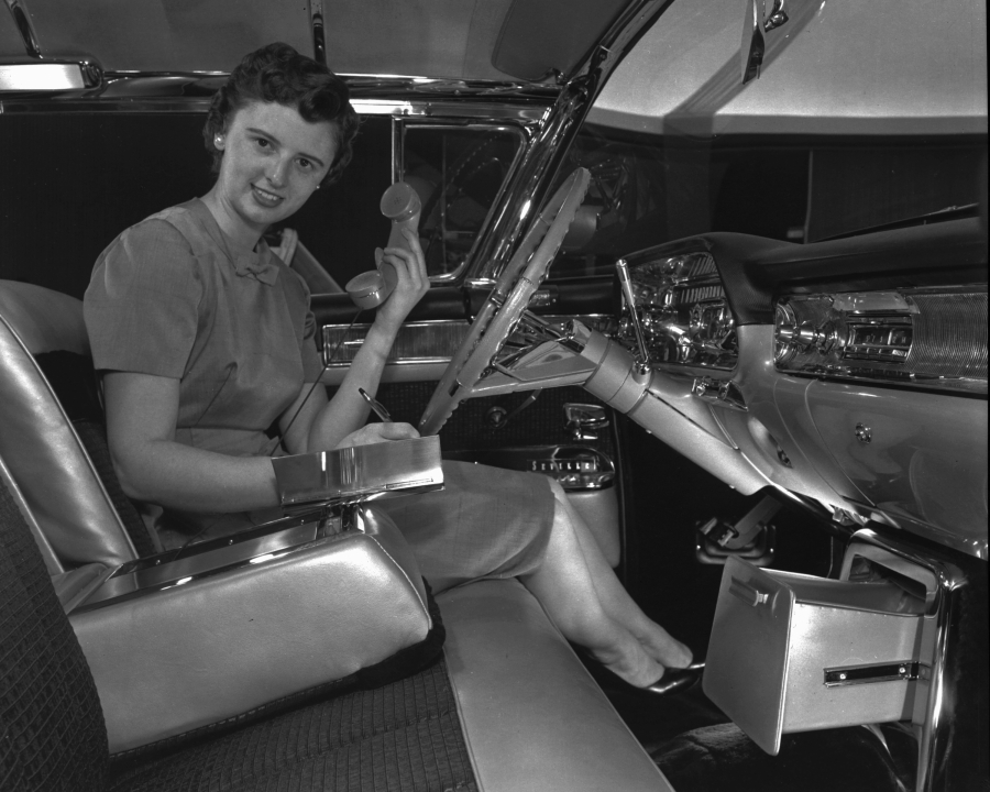 Suzanne Vanderbilt demonstrating an early car phone and built-in memo pad — custom features for her 1958 exhibition-model Cadillac Eldorado Seville.