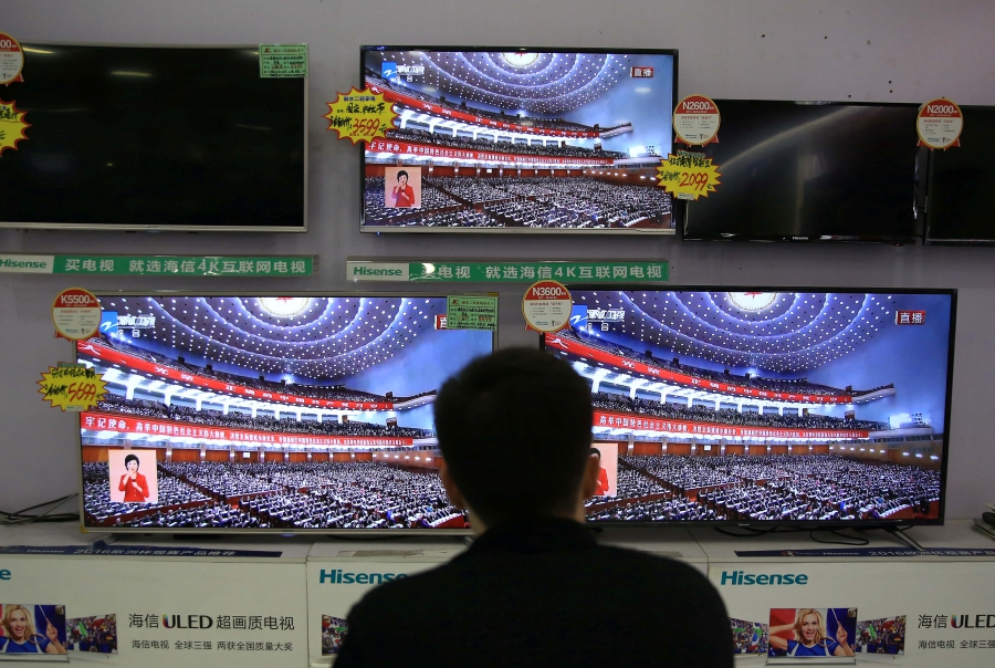 A man watches a broadcast of Chinese President Xi Jinping delivering his speech during the opening of the 19th National Congress of the Communist Party of China.