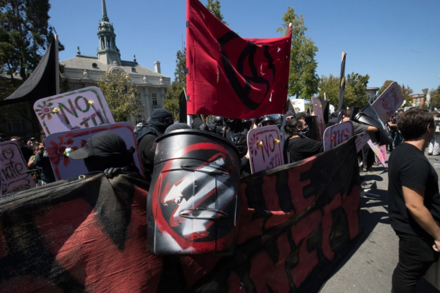 Three downward arrows, shown on an antifa activist's shield, also is a symbol of the far-left movement.