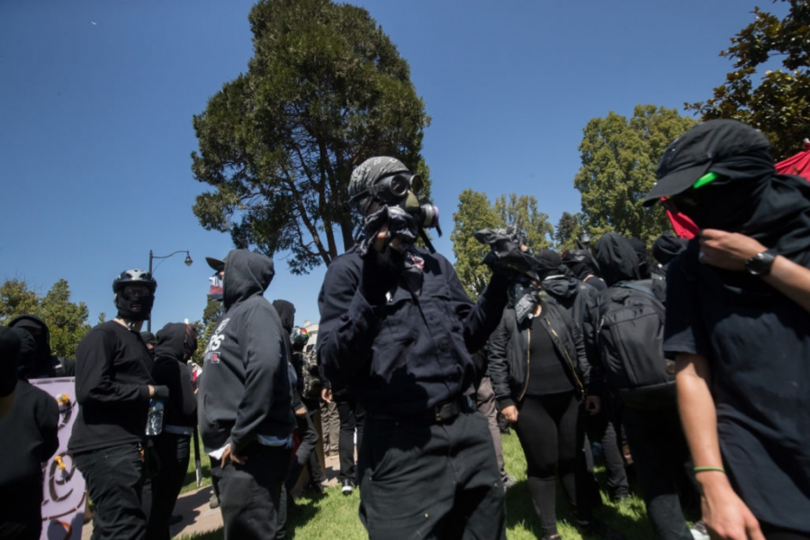 """Members of the anti-fascist movement form a """"black bloc"""" — moving in formation, wearing black — to protect the Aug. 27 march on a planned right-wing rally in downtown Berkeley, Calif."""