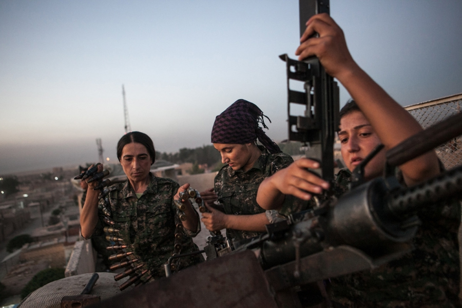 YPJ fighters load a weapon in Syria.