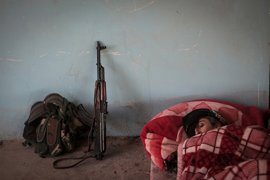 A YPJ soldier sleeps in an abandoned Iraqi Army outpost on the outskirts of Rabia.