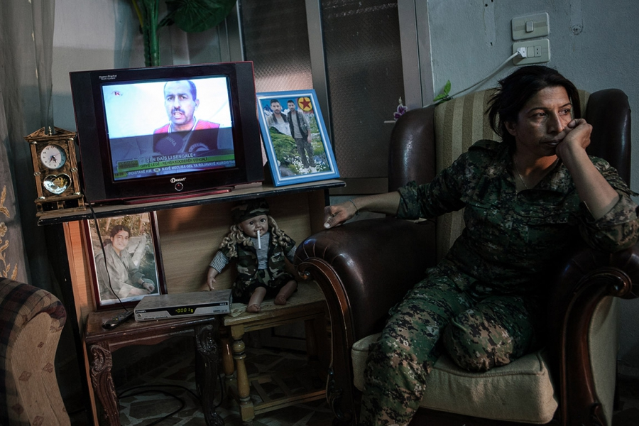 A YPJ soldier sits at a military base in Syria.