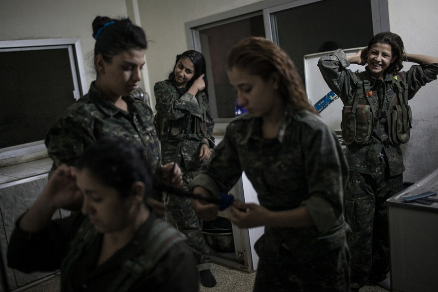YPJ recruits fix their hair before drills in Syria.