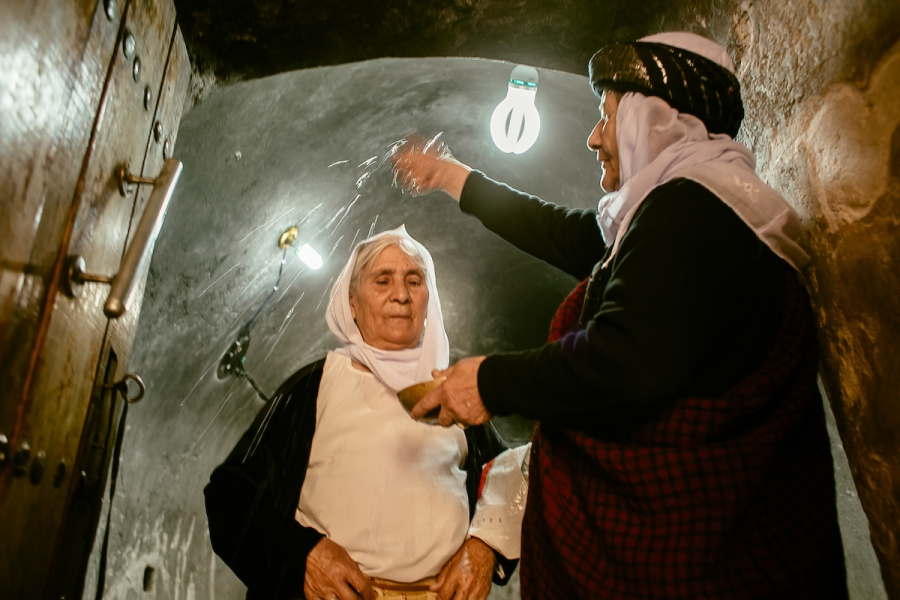 Yazidi religious leader Asmar Asmail pours water on the head of Hure Kaso Murad, a key step in the reintegration ritual after she was forcibly converted to Islam.