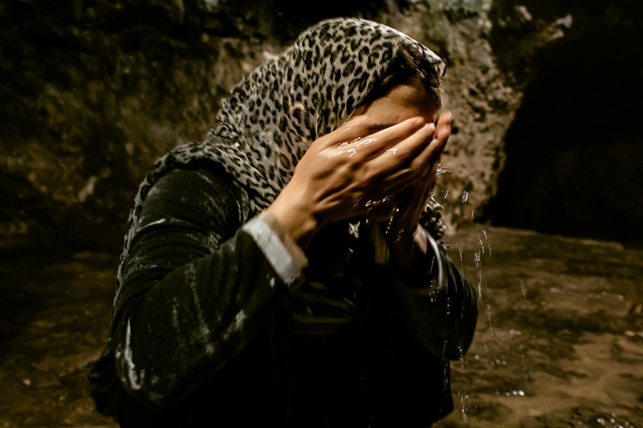 Turkia Hussein washes her face with sacred waters of the fountain. She is Yazidi again.