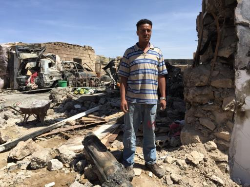 Ayman al-Sanabani stands outside the wreckage of his family's home.