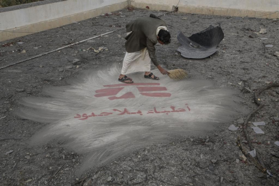 A hospital guard sweeps away debris from an airstrike. The roof of the hospital had been painted with the logo of Doctors Without Borders so that jets conducting airstrikes would know this facility was being run by the international aid organization.