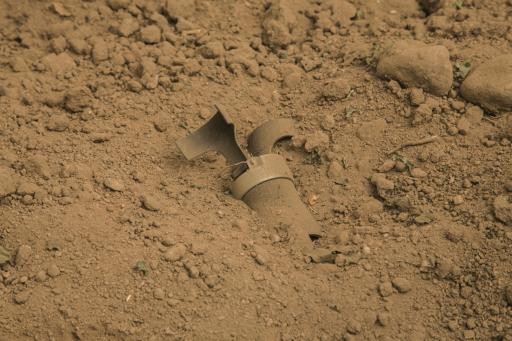 A cluster munition believed to be made in Brazil lies half buried in a cucumber field in Sadaa, Yemen.