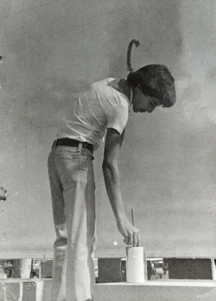 A 1981 photo of Angel Boligán, then around 16, painting a mural in his hometown of San Antonio de los Baños, Cuba.