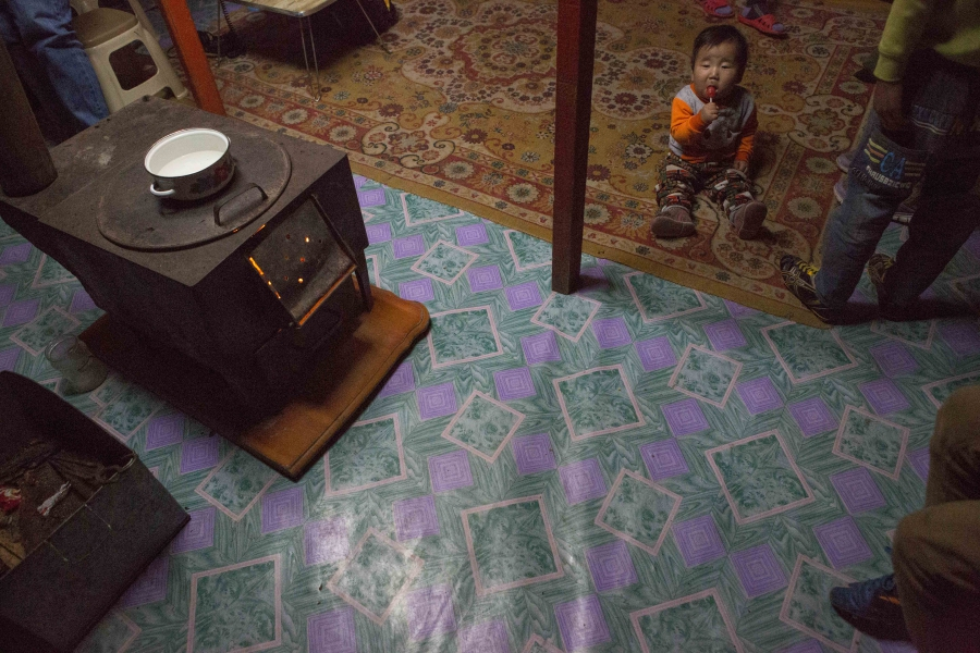 Eight month-old Munkh-erdene sits next to his family's traditional stove in thier ger, or yurt in Ulaanbaatar. The stoves are meant to burn wood or animal dung, but many families use them to burn coal, causing a spike in air pollution in the winter.