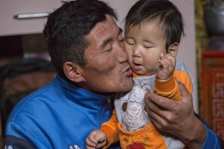 Jargalsaikhan Erdene-Bayar holds his eight-month-old son Munkh-erdene inside his family's ger in Ulaanbaatar. Erdene-Bayar herded livestock in the countryside until a harsh winter killed most of his animals and forced him to look for work in the city.