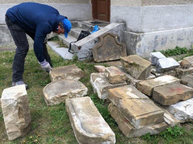 A man restoring headstones.