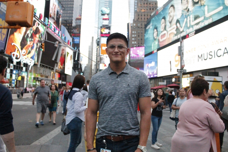 Man standing in Times Square, smiling