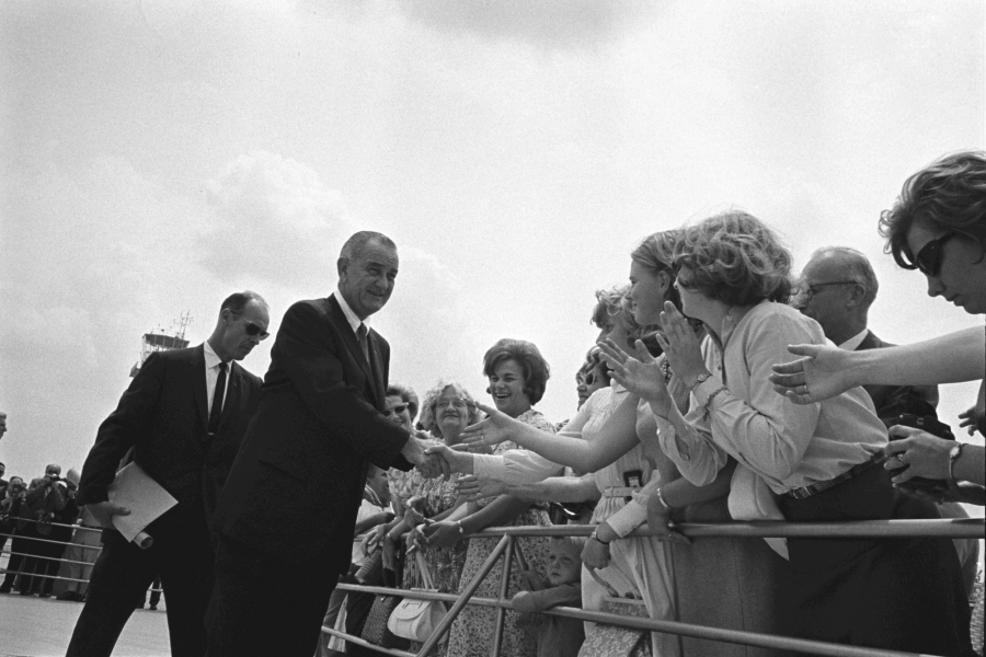 President Lyndon B. Johnson greets crowds, USSS Agent Rufus Youngblood is behind him.