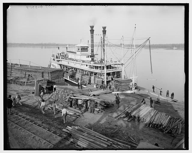 A historic photograph of prisoners at work between 1900 and 1910, carrying lumber from a dock onto a ship in the Mississippi River near Angola prison.