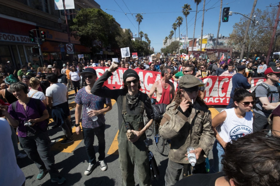 Antifa members John Cookenboo, center, with fist raised, and Vincent Yochelson, right, in green cap, attend an Aug. 26 anti-hate rally in San Francisco.