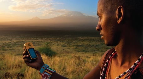 Lion Guardian Ng'ida takes a GPS point in front of Mt. Kilimanjaro. GPS data helps Lion Guardians track animals and keep livestock out of harm's way.