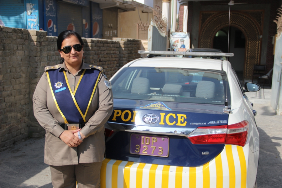 Asima Naqvi stands with her patrol car.