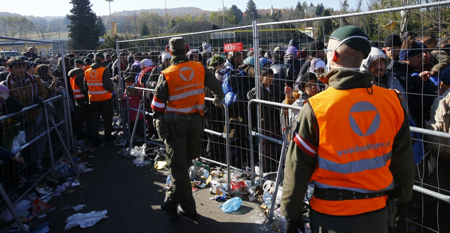 Austrian army soldiers observe migrants as they wait to cross the border from the village of Sentilj, Slovenia into Spielfeld, Austria, Nov. 2, 2015.