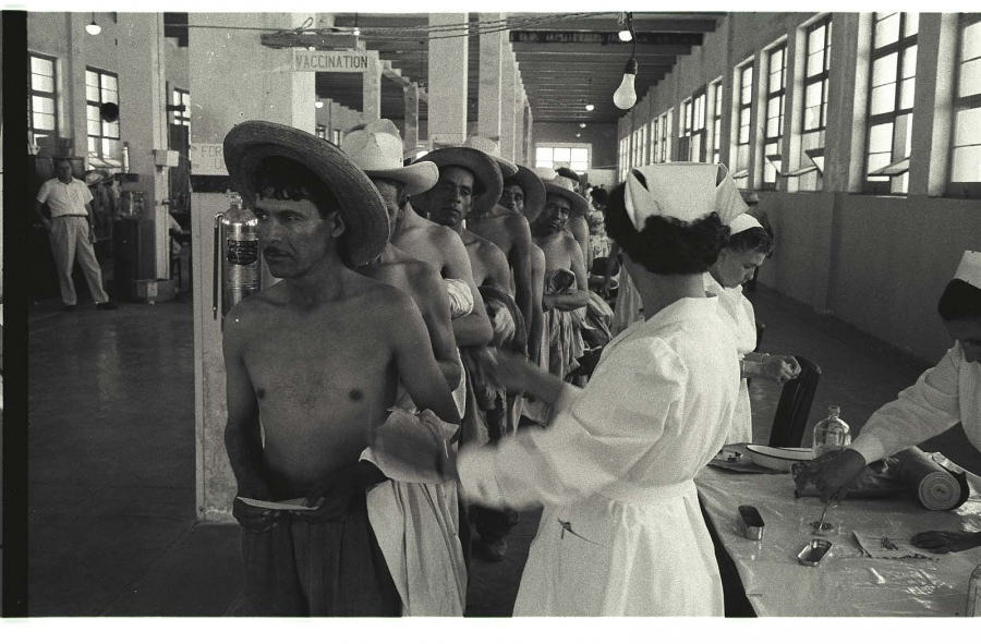 Men without shirts and wide-brimmed hats line up in front of a nurses' table.