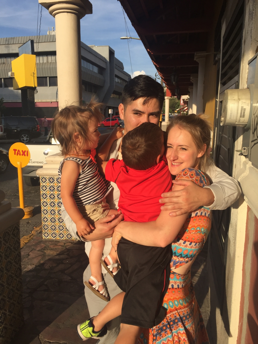 Two adults and two small children hug in circle, standing on sidewalk