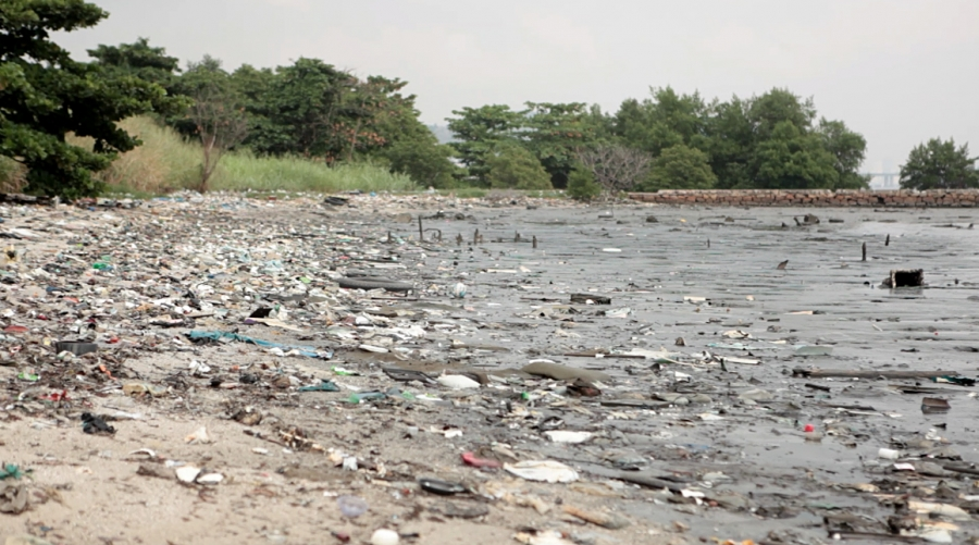 The shoreline along Guarabana Bay, near Rio de Janeiro, is littered with debris and trash. The water in the bay itself is murky brown due to oils spills and other pollutants, activists say.