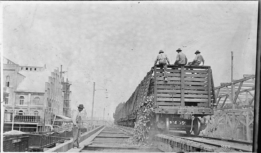 Workers sit on large crate on tracks, with vegetables spilling out, as another worker looks on. Black and white photo.