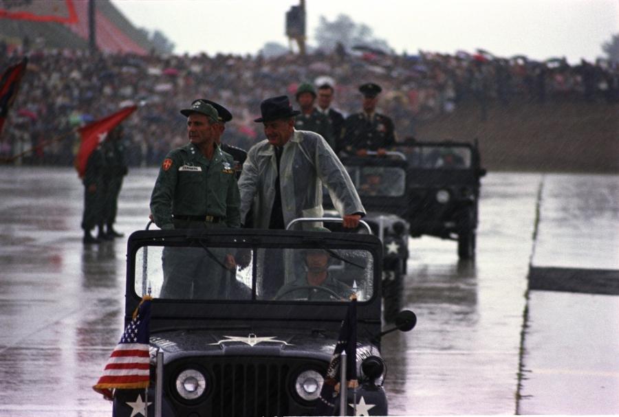 Standing in a jeep during a rainstorm (L-R:) Maj. Gen. Ben Sternberg, Pres. Lyndon B. Johnson