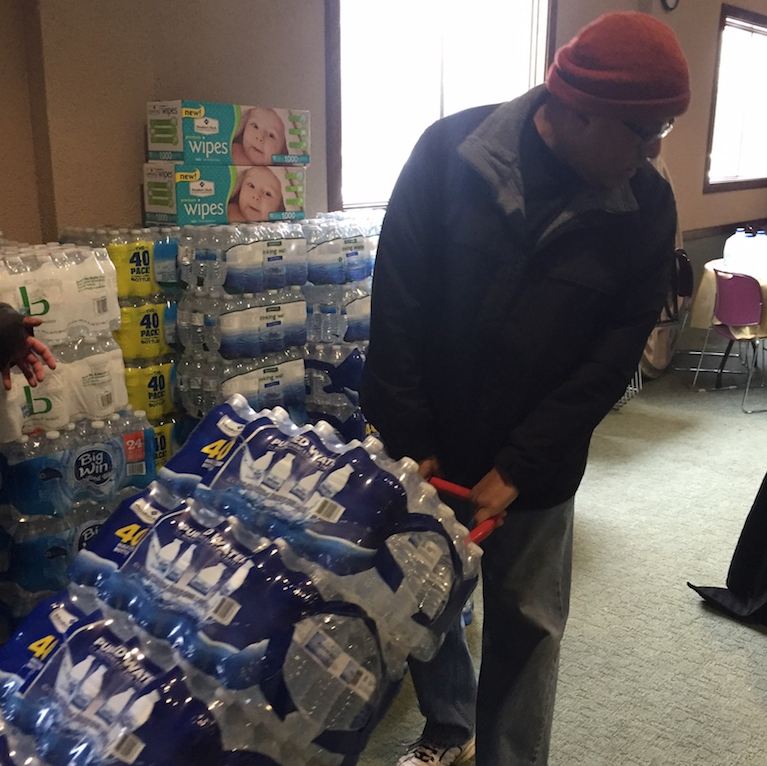 A volunteer hauls water off a truck in Flint, Michigan