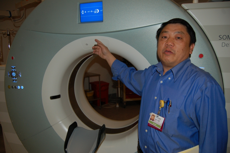 Changvang Her demonstrates how a CAT Scan machine at Mercy Medical Center plays an automated recording of his voice giving directions in Hmong — for when he's not around to translate.
