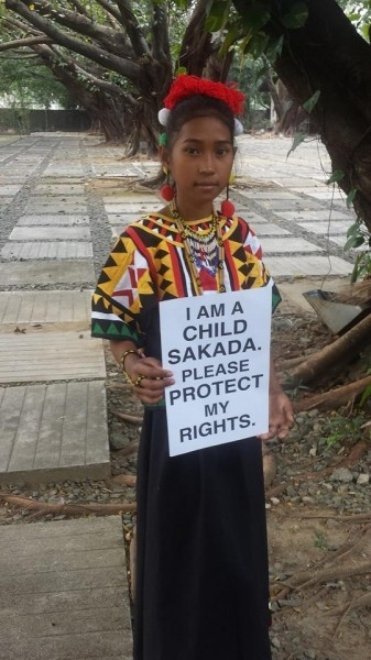 """Pitang holding a placard which reads: """"I am a child laborer"""". Photo from the Facebook page of Jhona Ignilan Stokes"""