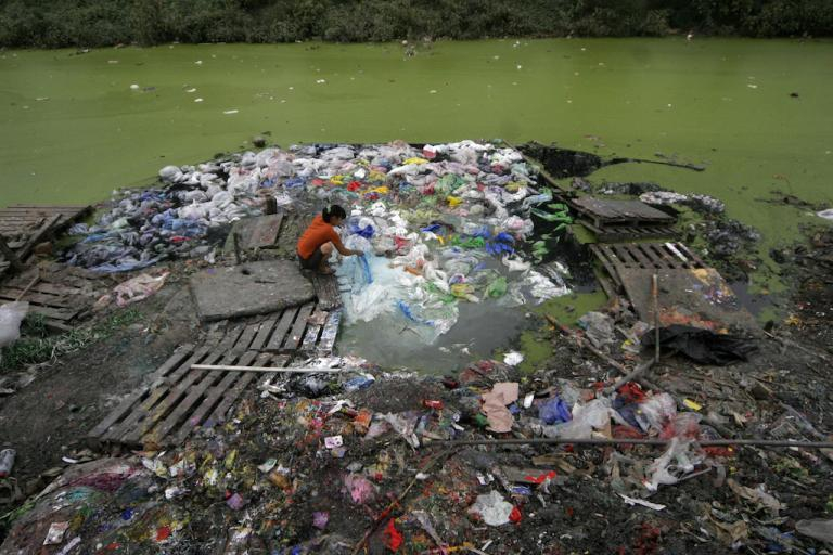A woman washes plastic in a river in Tianjin, China, Sept. 13, 2007.